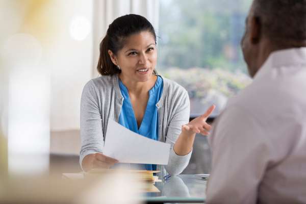 A cheerful mid adult female therapist sits at a table across from a new unrecognizable male client.  She  gestures as she explains her goal and counseling strategy.