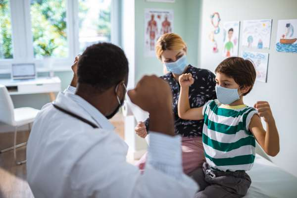 Close up of a Black male pediatrician and a white female physician assistant having a check up on their patient.