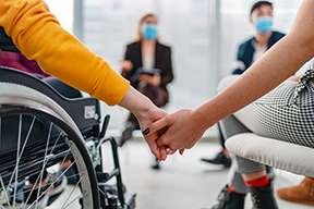 A person in a chair and a person in a wheelchair hold hands while sitting in a circle of people talking.
