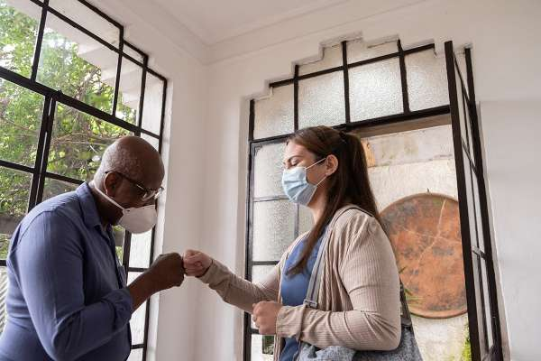 Home caregiver arriving in patient's house and greeting with fist bump - wearing face mask