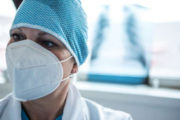A female medical professional wearing a mask and cap stands in front of some chest xrays.